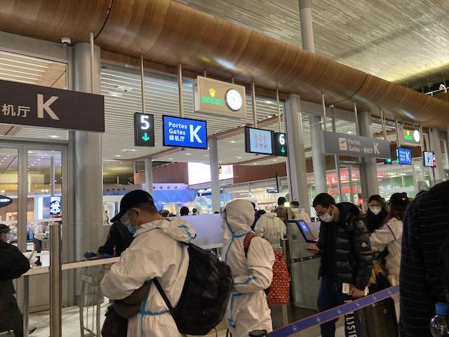 防護服を着て並ぶ人、パリド・ゴール空港
